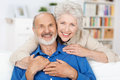 Affectionate elderly couple with beautiful beaming friendly smiles posing together in a close embrace in their living room Royalty Free Stock Images