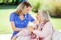Affectionate granddaughter and grandmother at looking each other on nursing home porch Stock Image