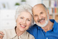 Affectionate happy retired couple with their heads together in a close embrace smiling at the camera Stock Images