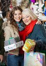 Affectionate mother and daughter with christmas presents standing at store Stock Photo
