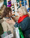 Affectionate mother and daughter embracing at with christmas presents shopping bags store Stock Image