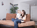 Affectionate mother and toddler exchanging a kiss young her at home on their couch in their living room Stock Photography