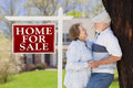 Affectionate senior couple front of for sale sign and house happy real estate Royalty Free Stock Photo
