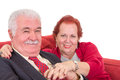 Affectionate senior couple on a red sofa sitting close together holding hands and looking at the camera with contented friendly Stock Photos