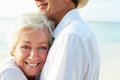 Affectionate senior couple on tropical beach holiday smiling to camera Royalty Free Stock Image