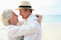 Affectionate senior couple on tropical beach holiday smiling to each other Royalty Free Stock Images