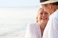 Affectionate senior couple on tropical beach holiday smiling to each other Stock Photo
