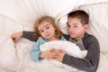 Affectionate young brother and sister lying in bed little cuddling together under the duvet looking up sleepily at the camera Stock Photos