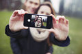 Affectionate young couple taking a self portrait with smartphone at the park mixed race teenage men and women outdoors Stock Image