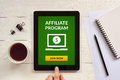 Affiliate program concept on tablet screen with office objects Royalty Free Stock Photo