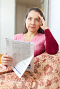 Affliction mature woman with newspaper wonder and at home Stock Image
