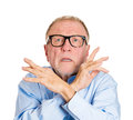 Afraid closeup portrait nerd senior mature man in black glasses looking scared shocked hands in air with x sign looking up Royalty Free Stock Photos