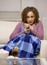 Afraid woman under blanket with remote control Royalty Free Stock Image