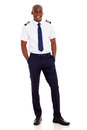 African airline pilot cheerful young standing over white background Stock Photography