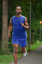 African american athlete running on a wooded path young footpath Royalty Free Stock Images