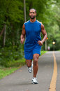 African american athlete running on a wooded path young footpath Stock Photos