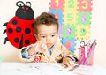 African American black boy drawing with colorful pencils in preschool a in kindergarten Royalty Free Stock Photo