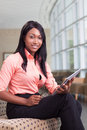 African american business woman sitting in lobby with computer tablet looking at camera smiling Royalty Free Stock Image