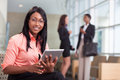 African american business woman women sitting in lobby with computer tablet looking at camera smiling two women in background Royalty Free Stock Photography