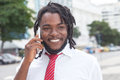 African american businessman with dreadlocks at phone in the city modern buildings background Stock Photography