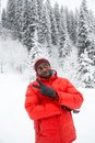 African American Cheerful black man in ski suit in snowy winter outdoors Royalty Free Stock Photo