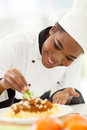 African american chef decorating happy in kitchen pasta dish Royalty Free Stock Photography