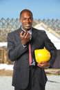 African american construction manager holding hardhat and radio at building site Royalty Free Stock Photography