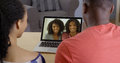 African american couple talking to family on laptop over video chat Royalty Free Stock Photo