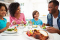 African american family eating meal at home together sitting down in kitchen chatting Royalty Free Stock Photography