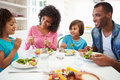 African american family eating meal at home together sitting down table having a conversation Royalty Free Stock Photos