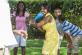 African american family playing baseball man woman boys girl children mother father son together outside the mother is batting Royalty Free Stock Photo