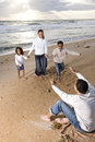 African-American family running to dad on beach Royalty Free Stock Photo