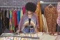 African American female designer measuring cloth at design studio