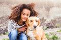 African american girl with her dog against concrete wall. Royalty Free Stock Photo