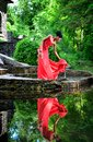 African American girl in a red dress with red shoes in hand is worth in the summer on the water on the stones in the Park Royalty Free Stock Photo