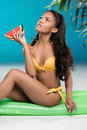 African american girl in swimsuit holding watermelon piece while sitting on swimming mattress Royalty Free Stock Photo
