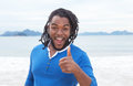 African american guy with dreadlocks at beach showing thumb up ocean and bright sky in the background Royalty Free Stock Photo