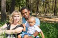 African American happy family: black father, mom and baby boy on nature. Royalty Free Stock Photo