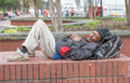 African american homeless man sleeping outside on bricks Royalty Free Stock Images