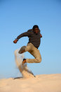 African american kung fu jumping an man showing a jump in the sand in front of blue sky background Royalty Free Stock Image