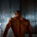 African american male body builder posing on a studio background. Back view Royalty Free Stock Photo