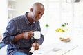 African american man eating breakfast and reading newspaper whilst holding hot drink Royalty Free Stock Images