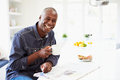 African american man eating breakfast and reading newspaper whilst holding hot drink smiling to camera Royalty Free Stock Photo