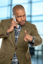 African american man using cellphone inside office building Royalty Free Stock Image