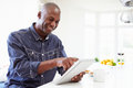 African american man using digital tablet at home pointing screen smiling Royalty Free Stock Photos