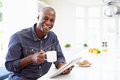 African american man using digital tablet at home smiling camera Stock Photos