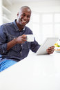 African american man using digital tablet at home whilst holding hot drink smiling camera Royalty Free Stock Image