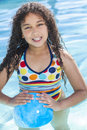 African american mixed race girl child in swimming pool a cute happy young playing a smiling with a blue ball Royalty Free Stock Images