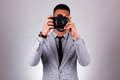 African american photographer holding a dslr camera black peop over gray background people Stock Image