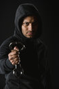 African american robber in zoodie and manacles isolated on black Royalty Free Stock Photo